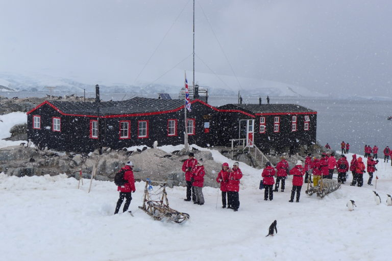 External view of Port Lockroy building with people, sledges and penguins